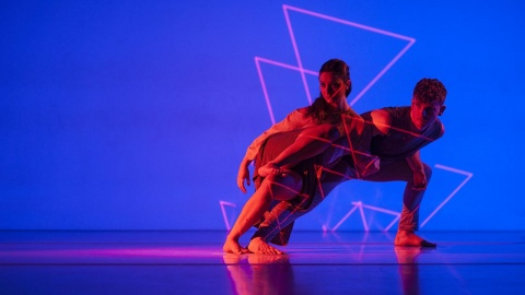 A full colour image showing two EDge dancers performing on a blue background lit with orange light and triangular projections. Image by Chris Nash and design by Mark Pepperall