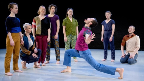 A full colour image showing a group of performers on stage watching a male dancer lunge with his arms out stretched and his tongue sticking out. Image by Camilla Greenwell