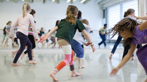 Young children dancing in a bright studio.