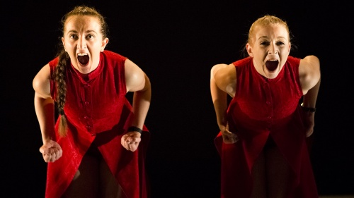 A full colour image showing two female dancers wearing red smocks bending towards the camera screaming with their fists clenched by their hips. Image by Alicia Clarke