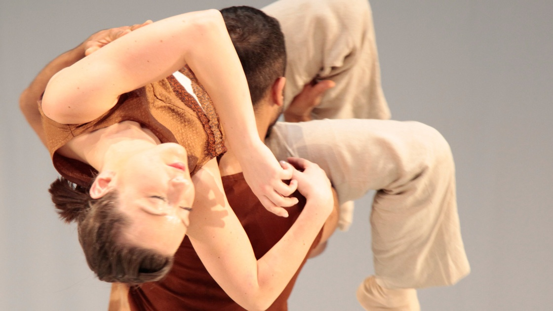 A full colour image of one male dancer with a female dancer draped over his shoulder. Image by Ivar Sviestins