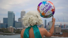 A figure wearing a blonde wig and sequined green dress holding a balloon faces a cityscape. We see this figure from behind.