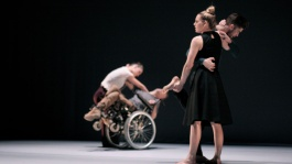 Exim Dance Company two performers are hugging and there's someone in wheelchair at the back. The photo is on stage (Photo by Claire Summers)