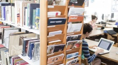 A full colour image showing a female student working at a laptop in the School library. Image by Hugo Glendinning