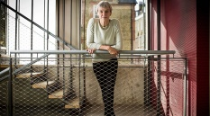 A full colour image of Siobhan Davies leaning on a handrail of a stairwell. Image by Felix Clay