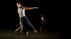 A full colur image showing a female dancer leaping across a stage. Image by Alicia Clarke